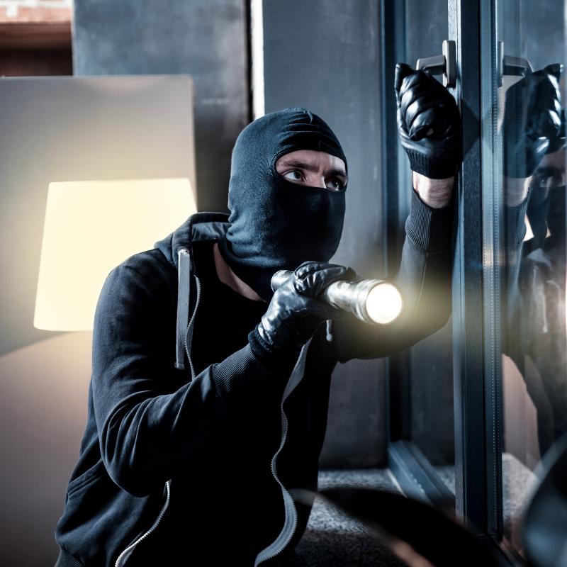Einbrecher beim Einbruch mit Taschenlampe